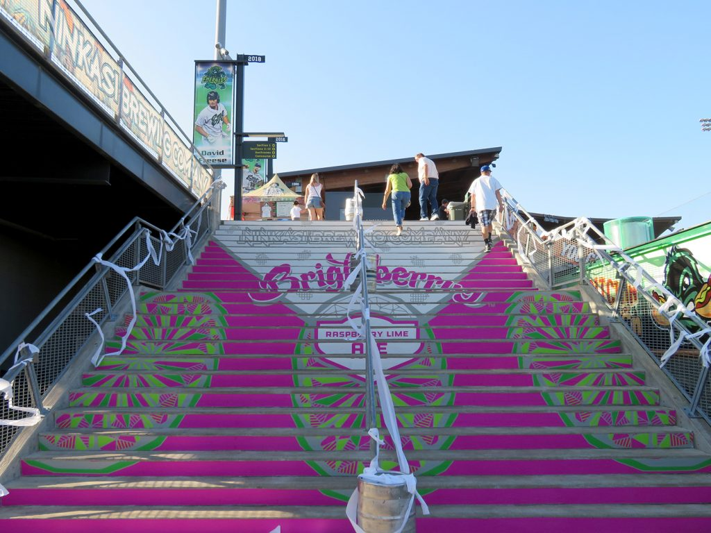 "A large concrete staircase with with bright pink and text that says ""Ninkasi Brewing Company Brightberry Raspberry Lime Ale."""