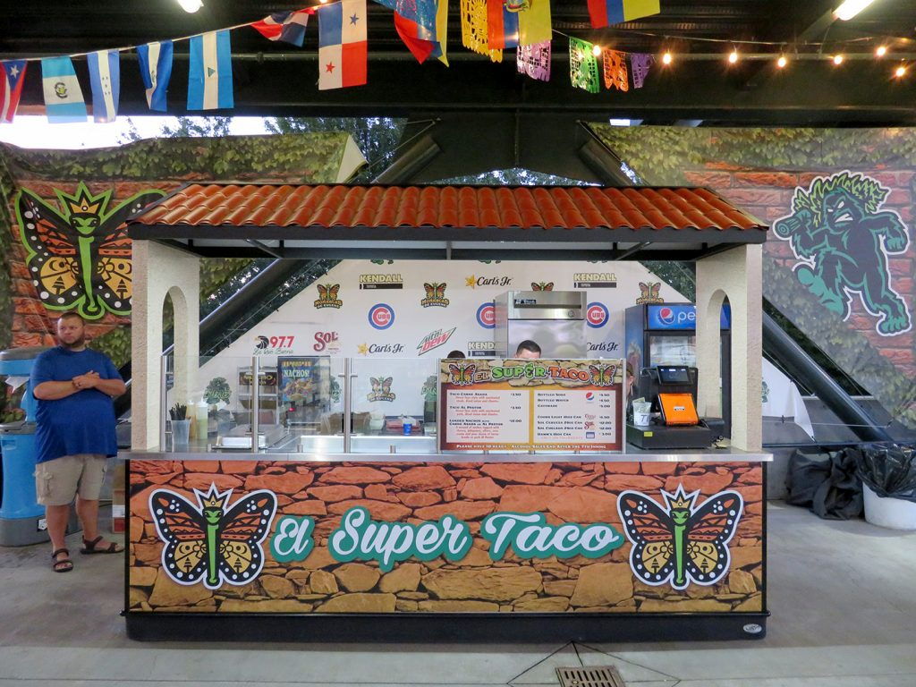 "A portable food cart decorated with monarch butterflies with text that says ""El Super Taco."""