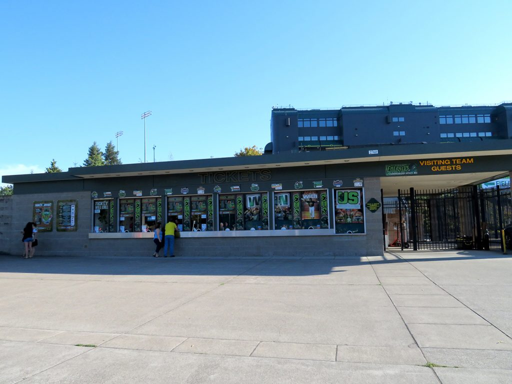 "Cinder block building with ""Tickets"" above multiple windows and the Eugene Emeralds logos plastered across the windows."