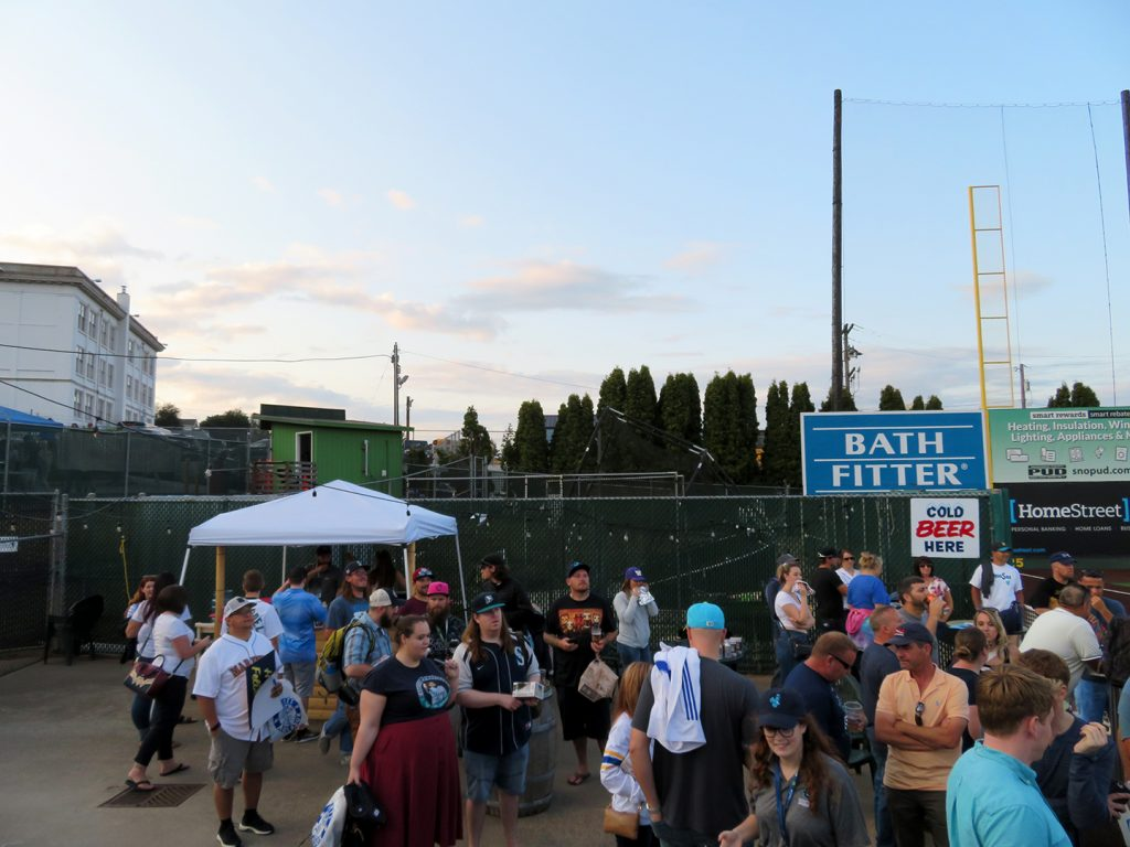 Several people stand around near a small canopy tent in the background serving beer at an Everett AquaSox baseball game.