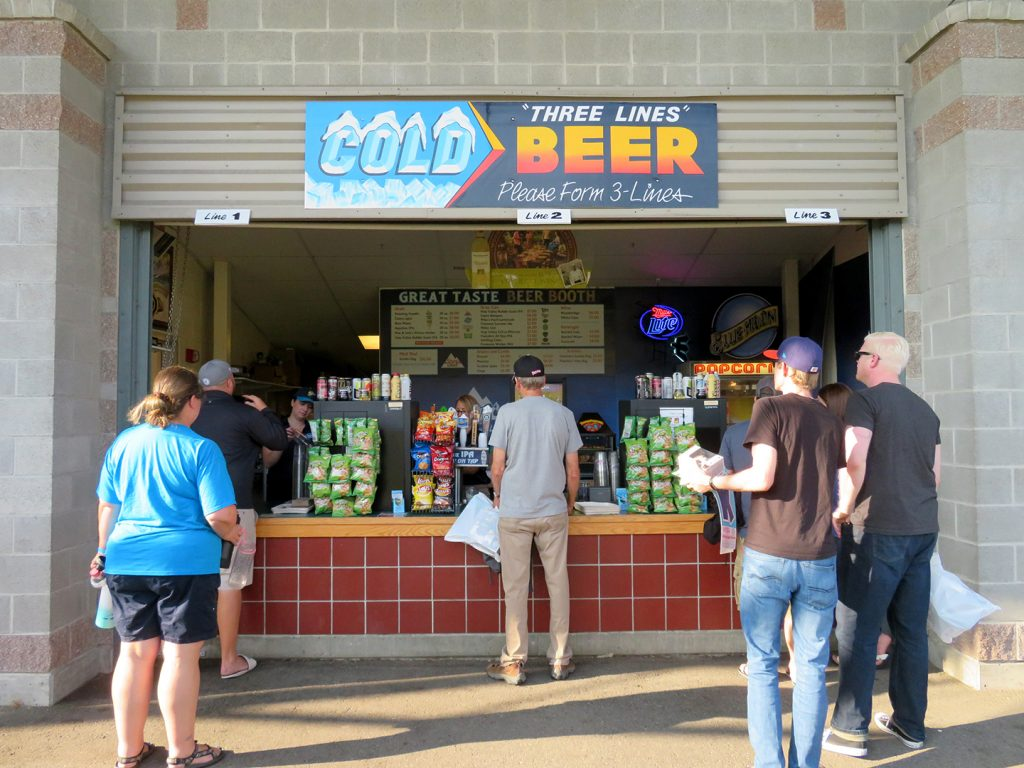 People stand in three lines in front of a beer concession stand at an Everett AquaSox baseball game.