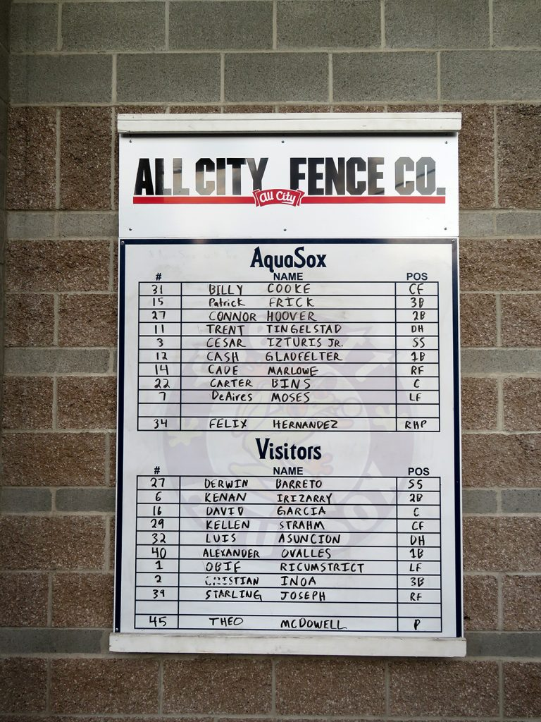 White board with starting lineups for Everett AquaSox and Spokane Indians on a cinder block wall.