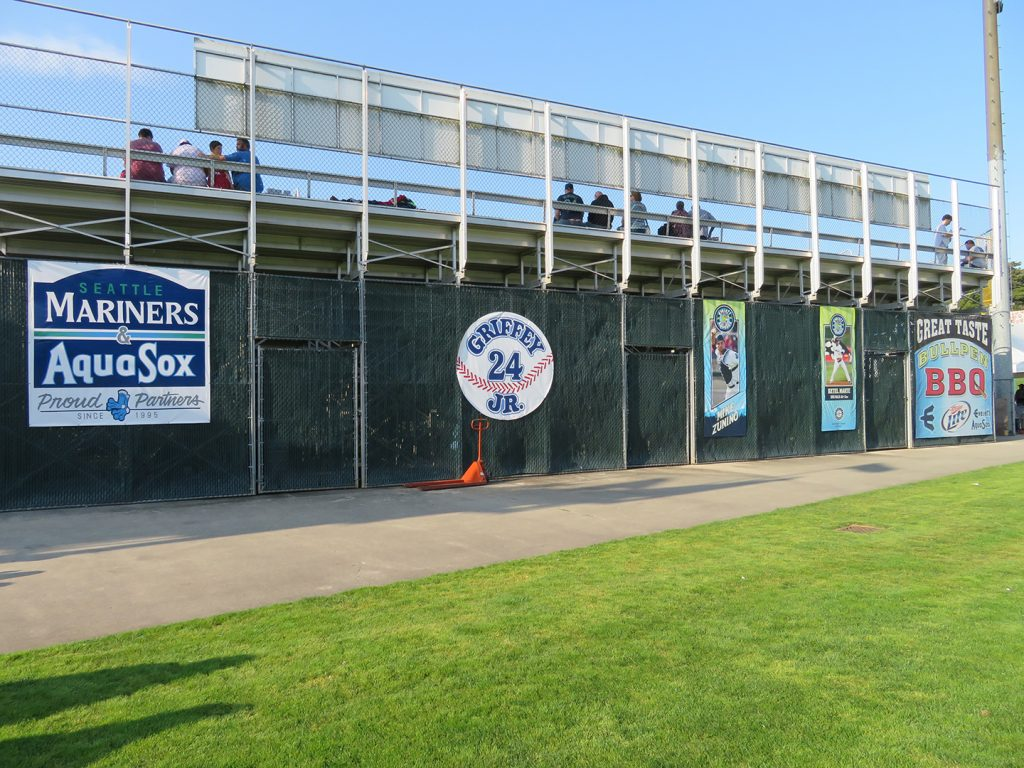 "Chain-link fence with a circular banner showing ""Griffey Jr. 24"" and two vertical banners showing former Everett AquaSox players Mike Zunino and Ketel Marte."
