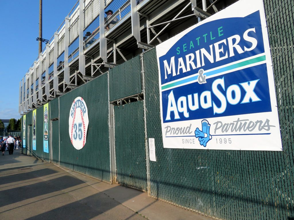 "Chain-link fence with a circular banner showing ""Spyder 35"" and three vertical banners showing former Everett AquaSox currently playing in MLB."