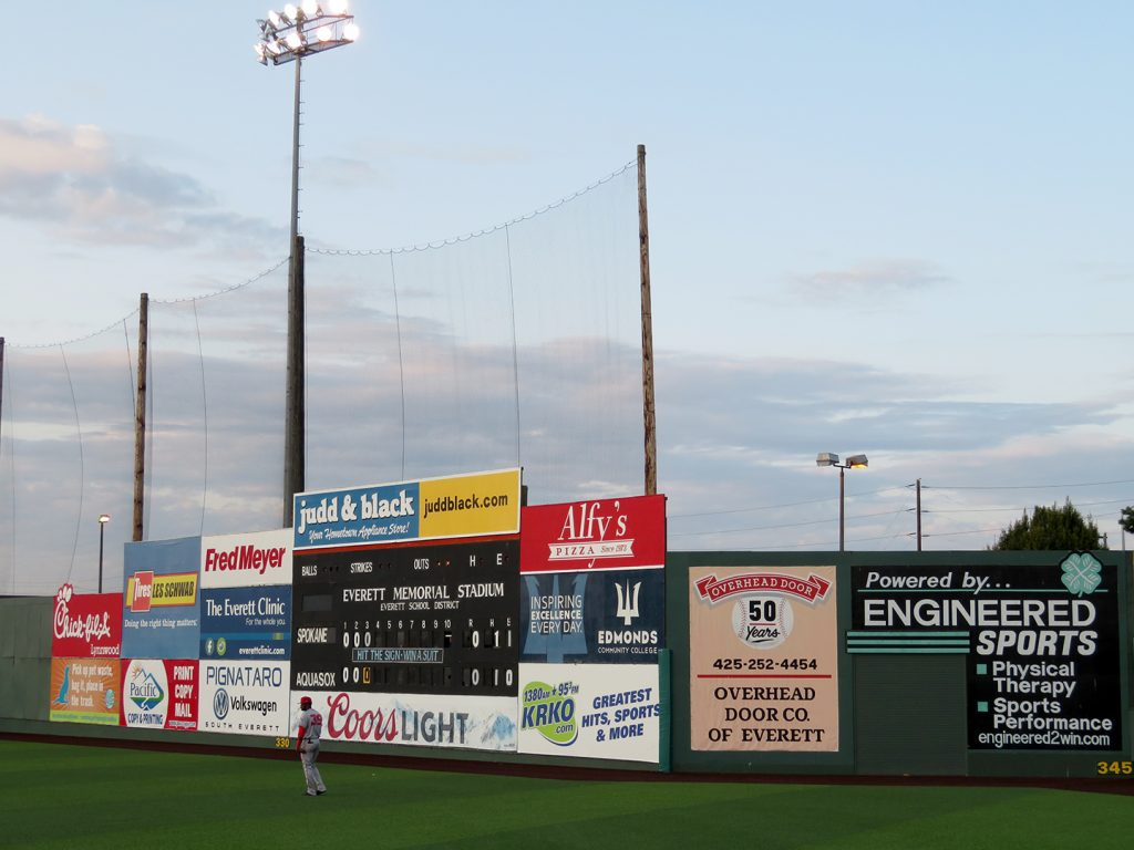 A baseball stadium outfield fence with multiple advertisements on it and a manually-operated scoreboard in the center of the image.