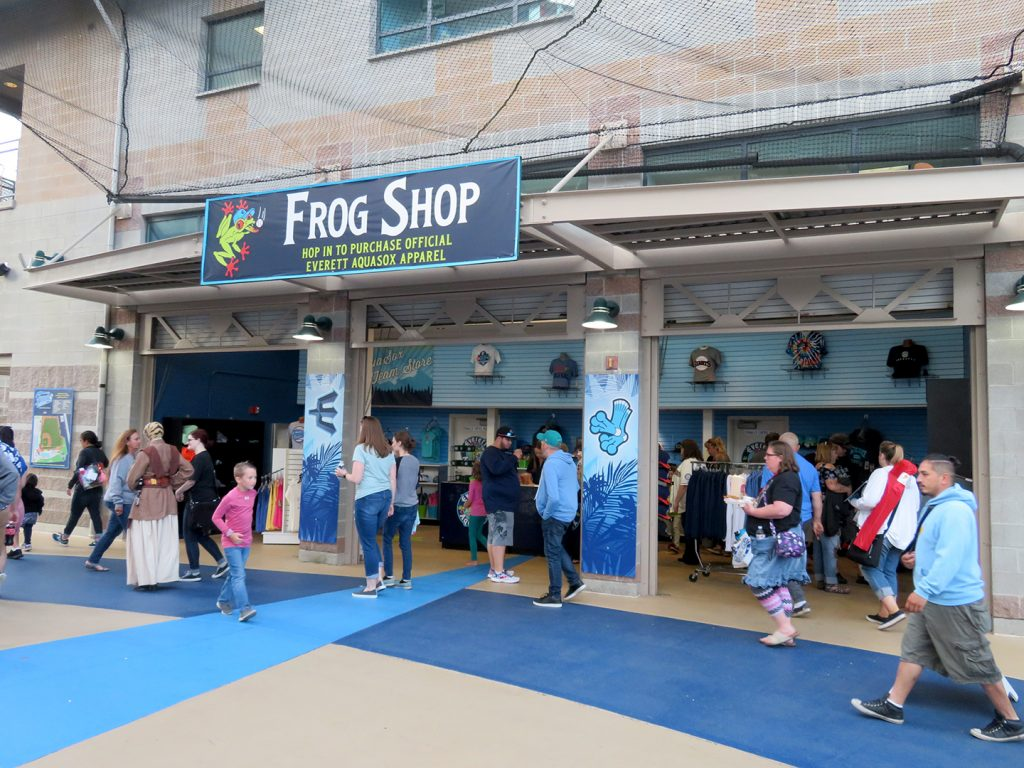 "Banner that says ""Frog Shop"" above three openings for the Everett AquaSox team store."