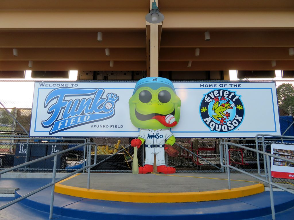 "A large Funko Pop! version of Everett AquaSox mascot Webbly stands in front of a banner that says ""Welcome to Funko Field"" and ""Home of the Everett AquaSox."""