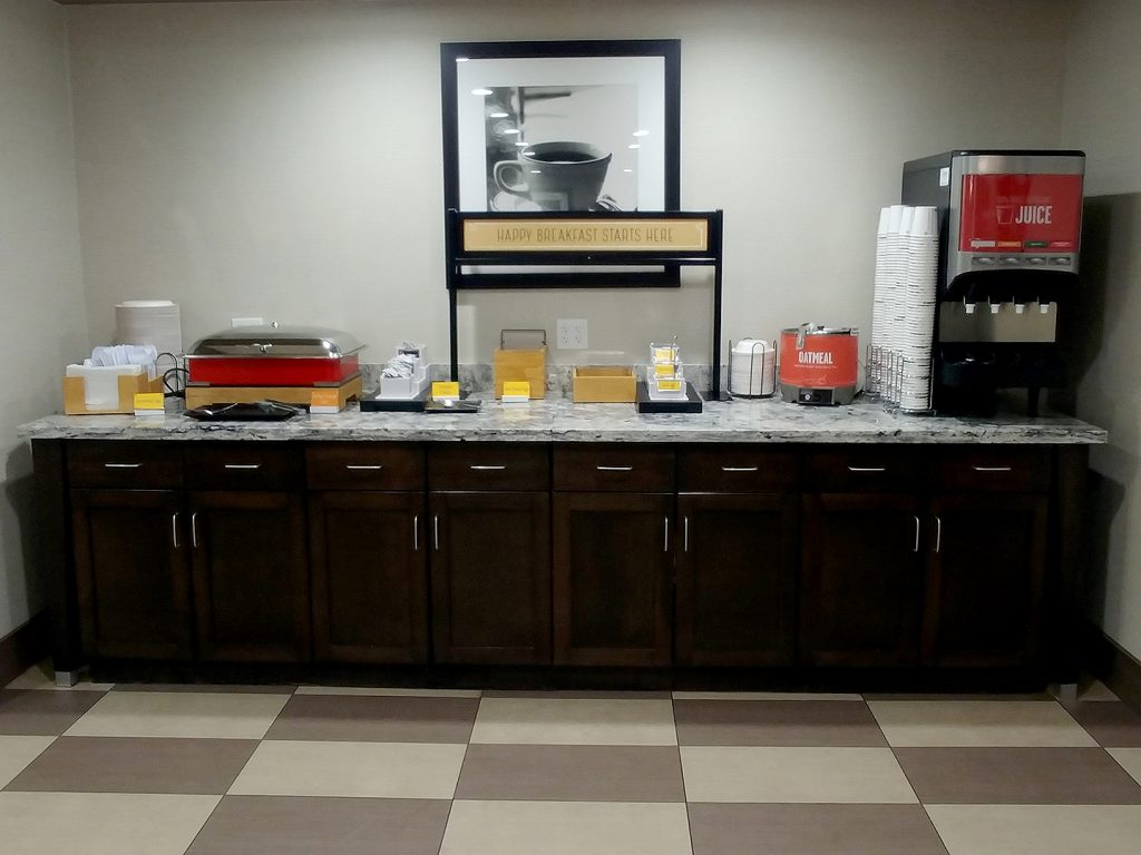 Four cabinets with a long granite counter and hot breakfast equipment on top.