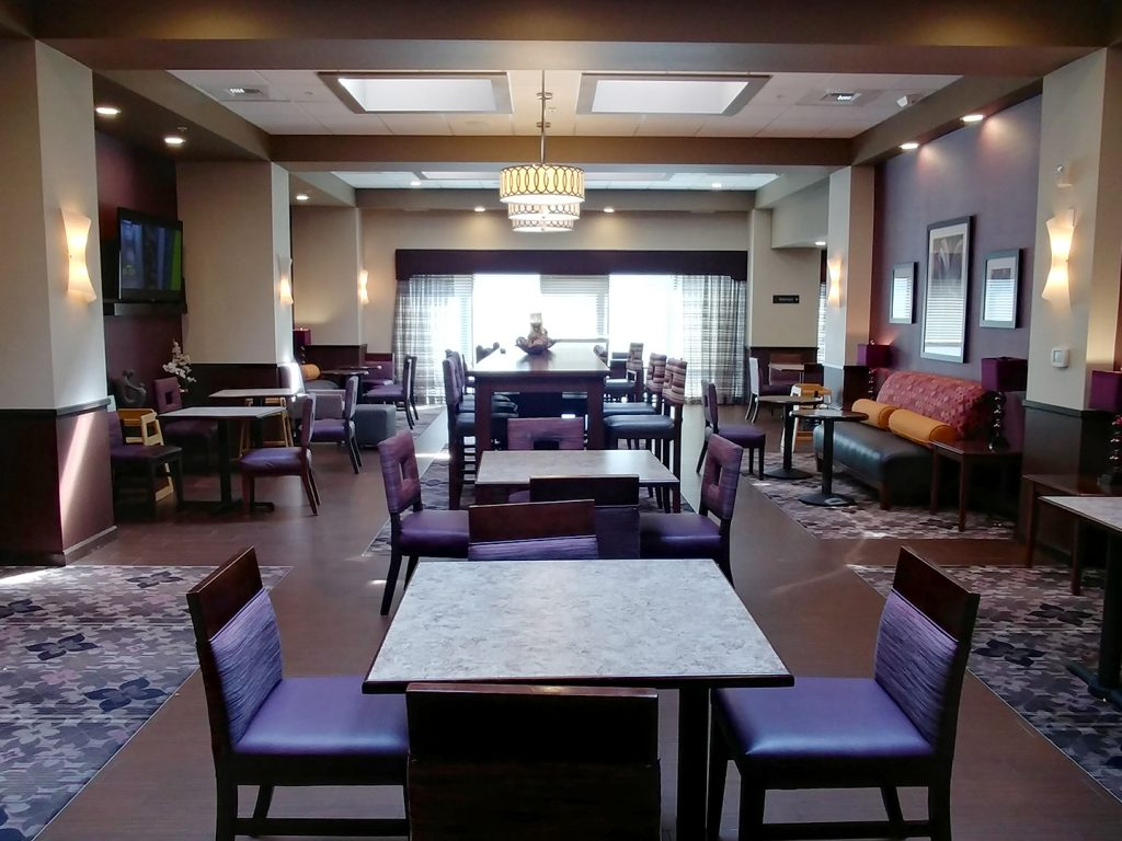 Overview of a large room with multiple tables and chairs including a high-top table for dining at the Hampton Inn Seattle/Everett.
