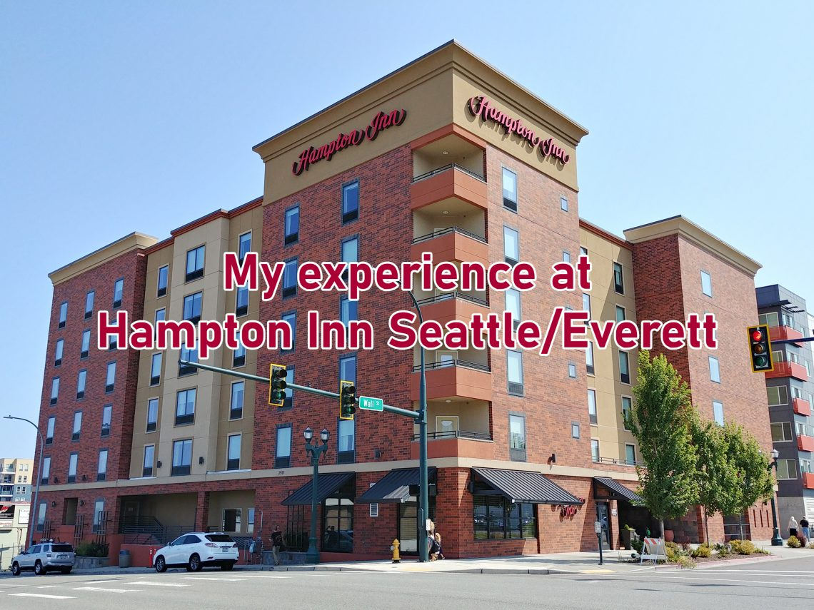 "Street corner with a large building and text overlaying image that says ""My experience at the Hampton Inn Seattle/Everett."""