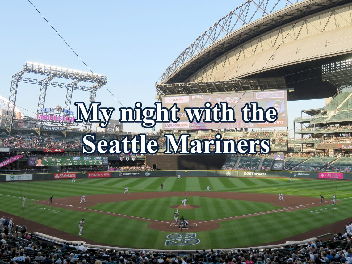 "View from behind plate during a baseball game with text overlaying the image that says ""My night with the Seattle Mariners."""