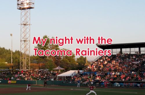 "View of a baseball stadium showing a pitcher on the mound with a grandstand behind him and Mount Rainier in the distance. Text overlaying the image says ""My night with the Tacoma Rainiers."""
