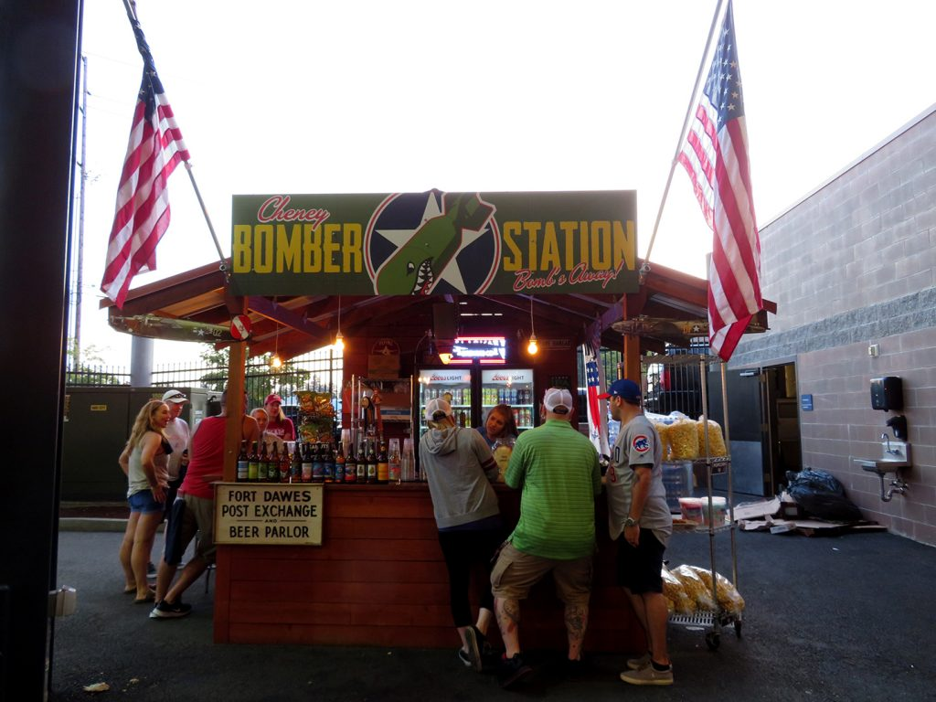 "A square, wooden booth with a sign above it that says ""Cheney Bomber Station"" with a green bomb in the middle of the sign. Several people are standing in line on the right side of the booth."