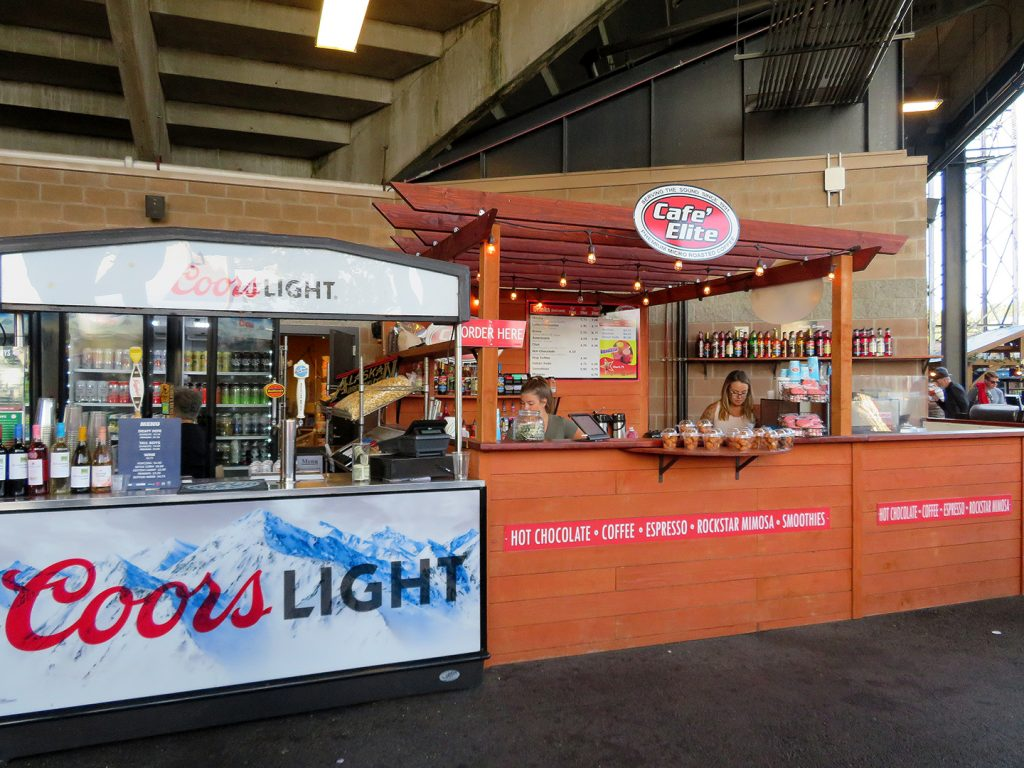 "A portable beer both with ""Coors Light"" signage next to a wooden concession stand called ""Café Elite."""