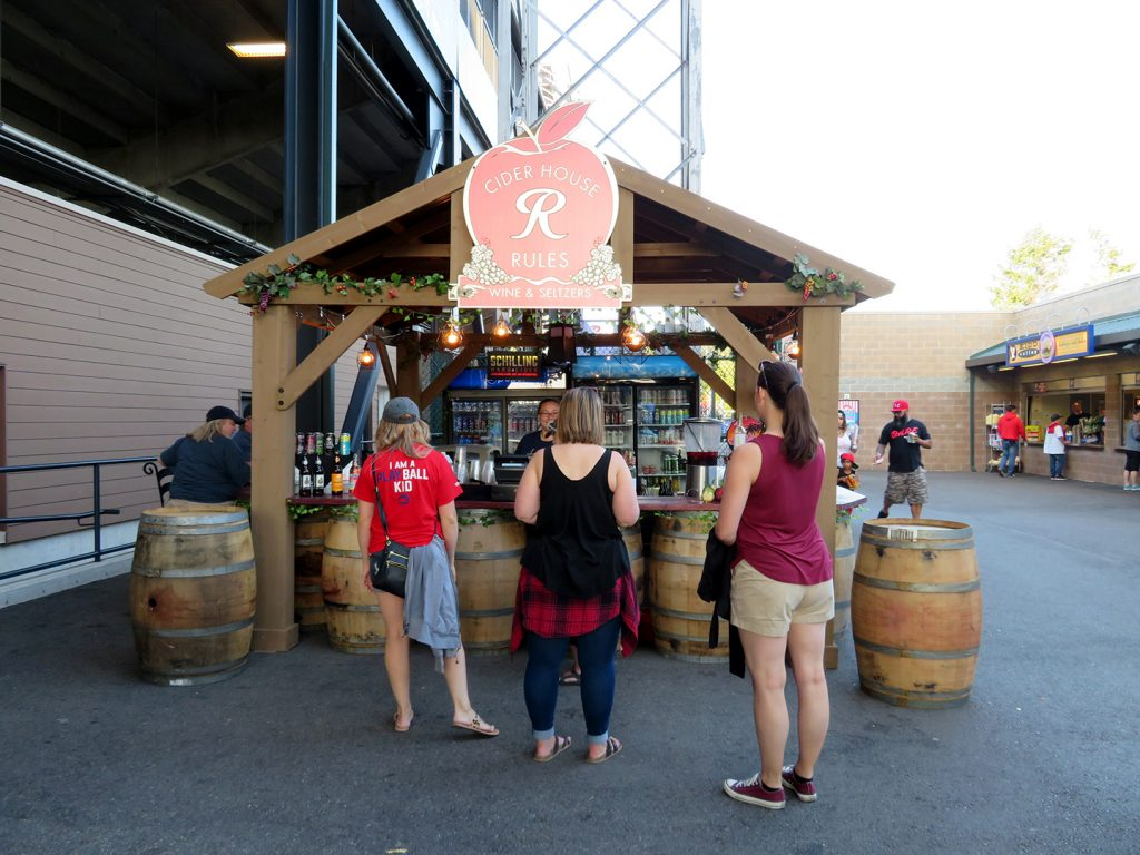 "A square, wooden booth with barrels in front of it and a sign shaped like an apple that says ""Cider House Rules."" Multiple people stand in front of the booth."