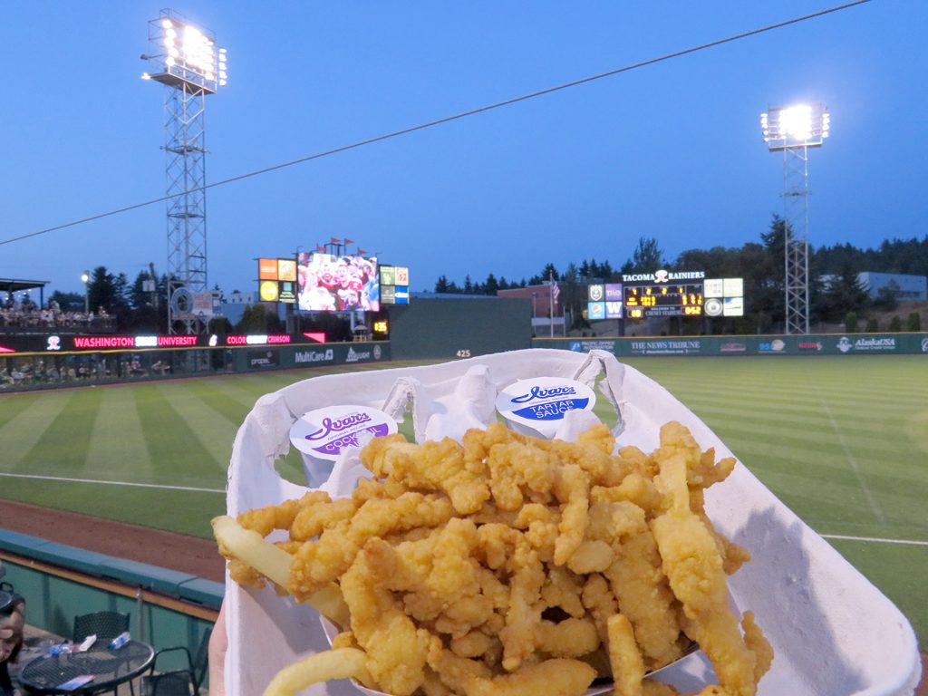 A basket of clam strips with a baseball field's videoboard and scoreboard in the background.