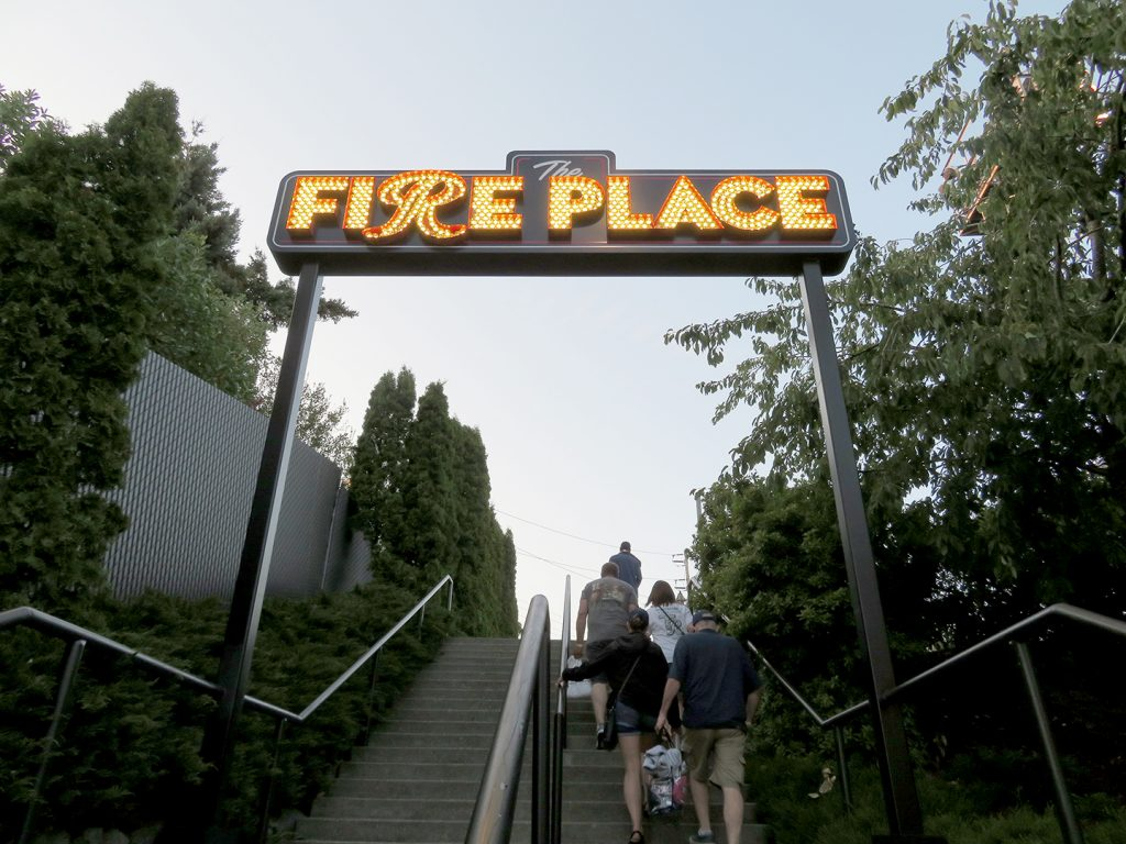 "People walking up stairs beneath a sign that says ""The Fireplace."""