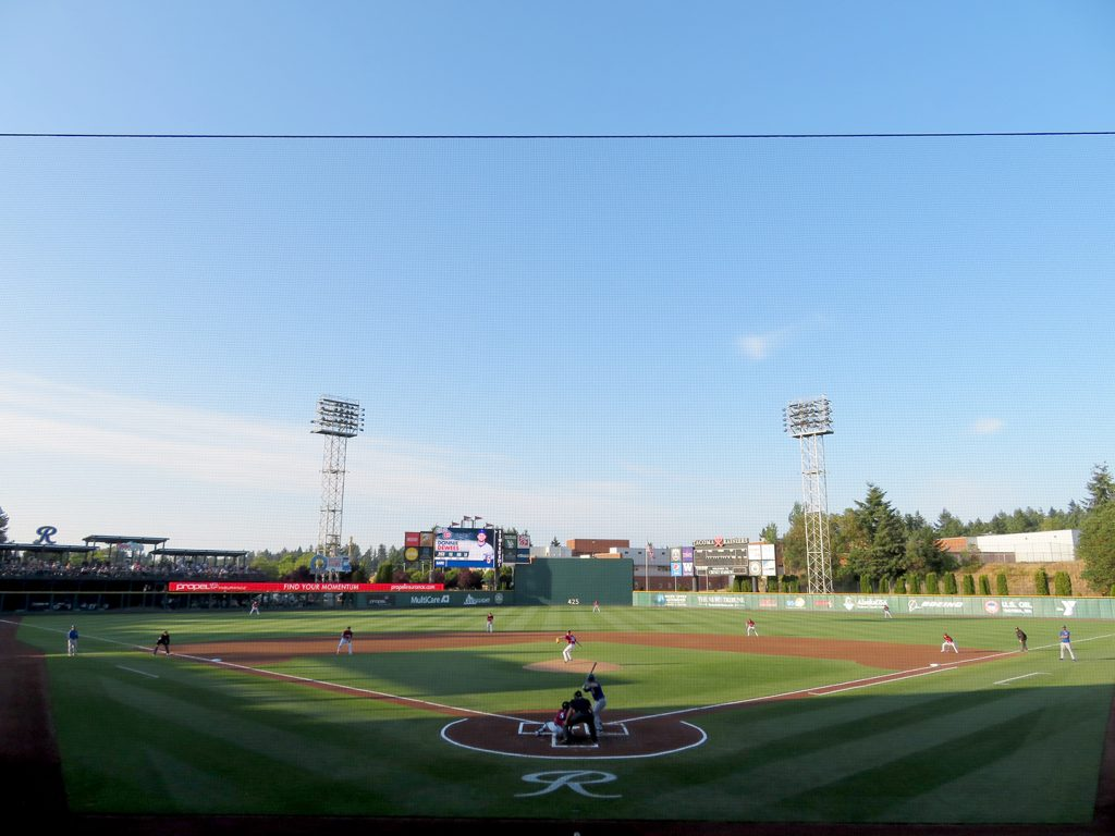 Overview of a baseball stadium with a pitcher throwing the first pitch of a Tacoma Rainiers baseball game between the Iowa Cubs and Tacoma Rainiers.
