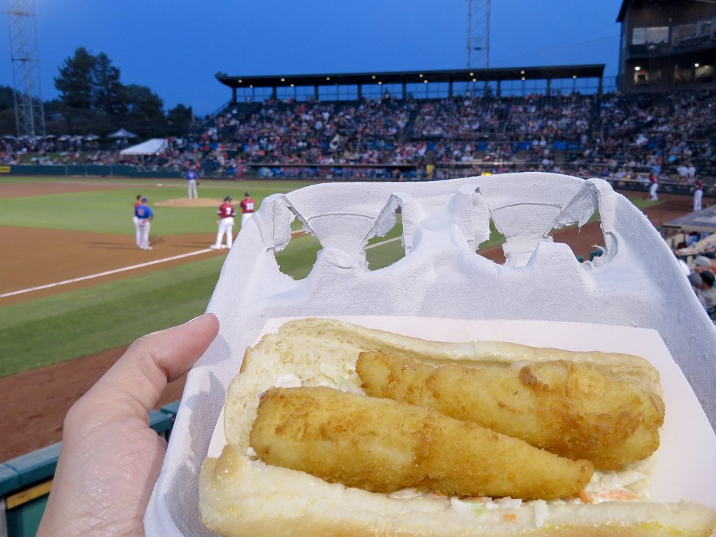 A cardboard tray with two piece of fried cod on a hot dog bun with a baseball stadium in the background.
