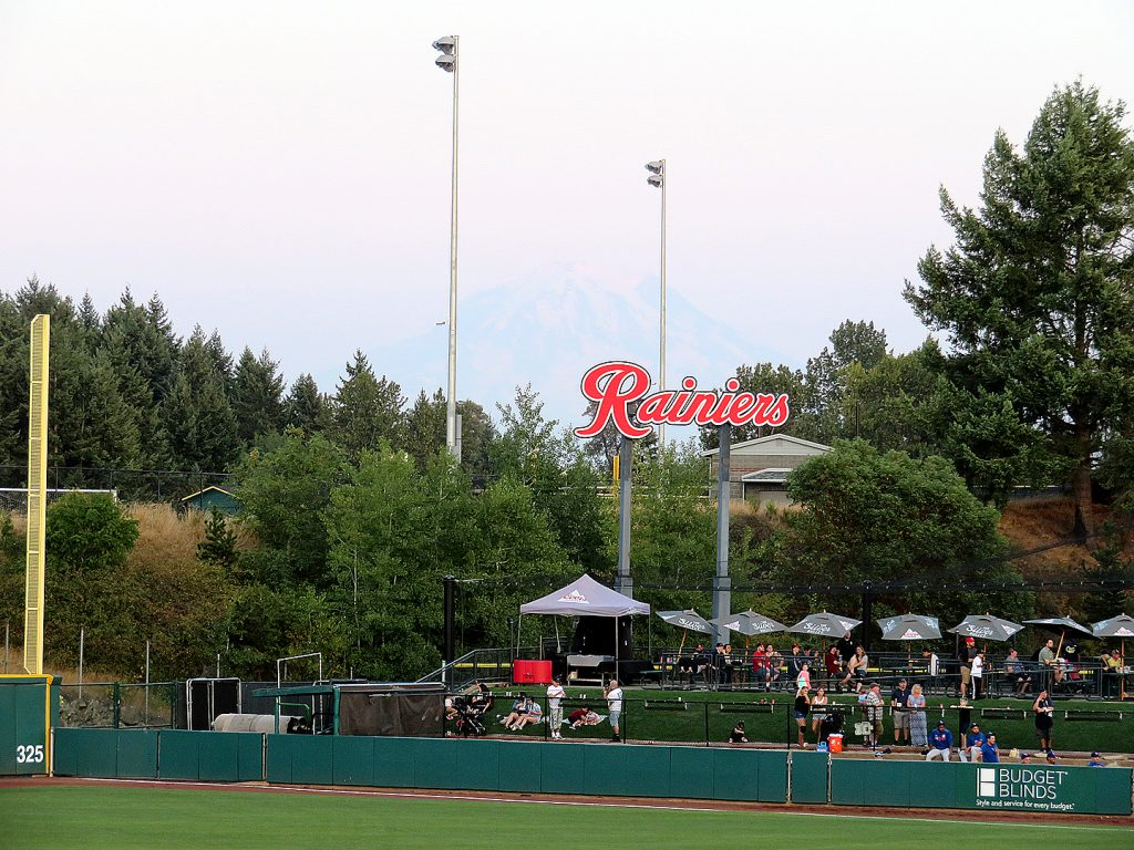 A cloudy sky with Mount Rainier in the distance and several people under canopy tents near a baseball field in the foreground.