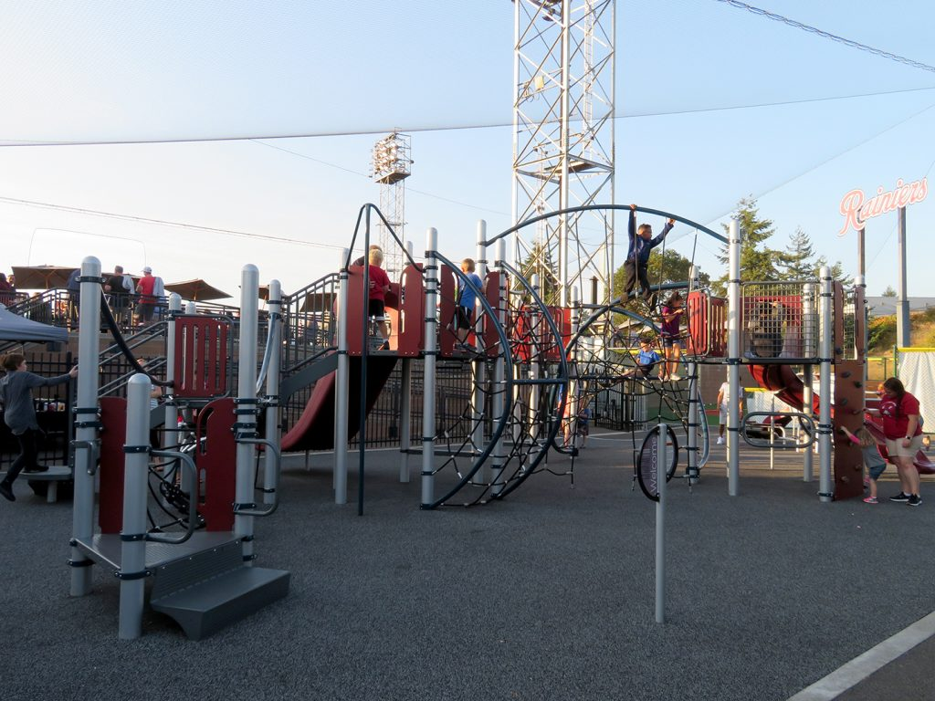Children play on a large playground set with a baseball field in the background.