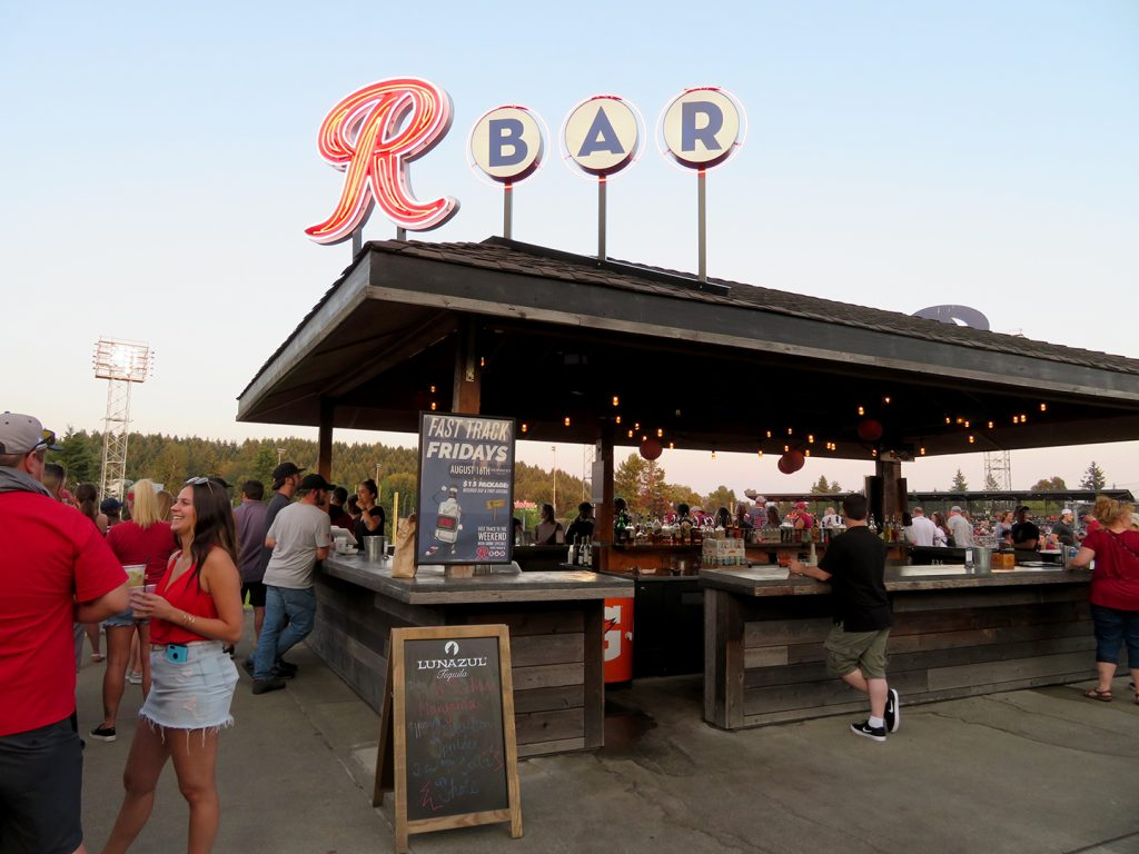 "Diagonal view of a large wooden bar with neon letters on the roof that spell out ""R Bar."""