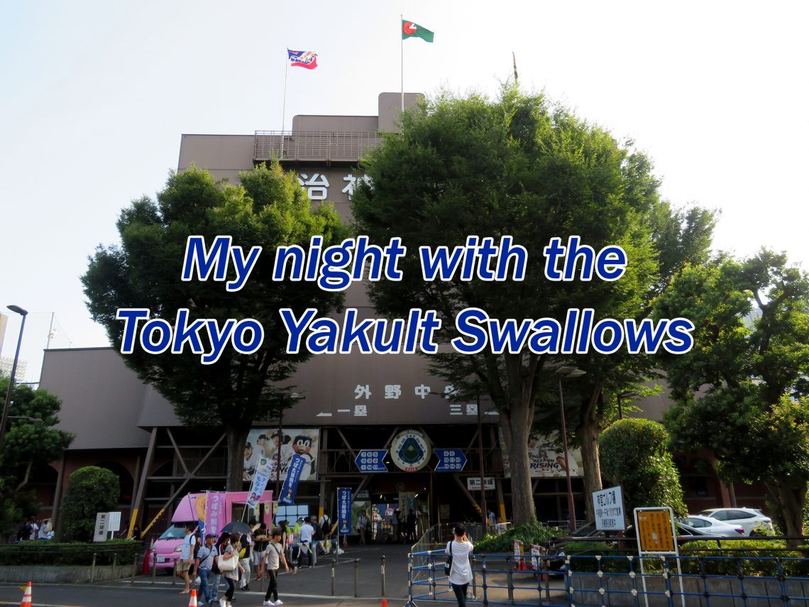 "Several trees in front of a large, grey concrete tower with text overlaying the image that says ""My night with the Tokyo Yakult Swallows."""