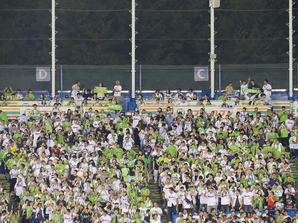 Several people stand in front of two rows of seats with 7/Eleven branding at a Tokyo Yakult Swallows baseball game.