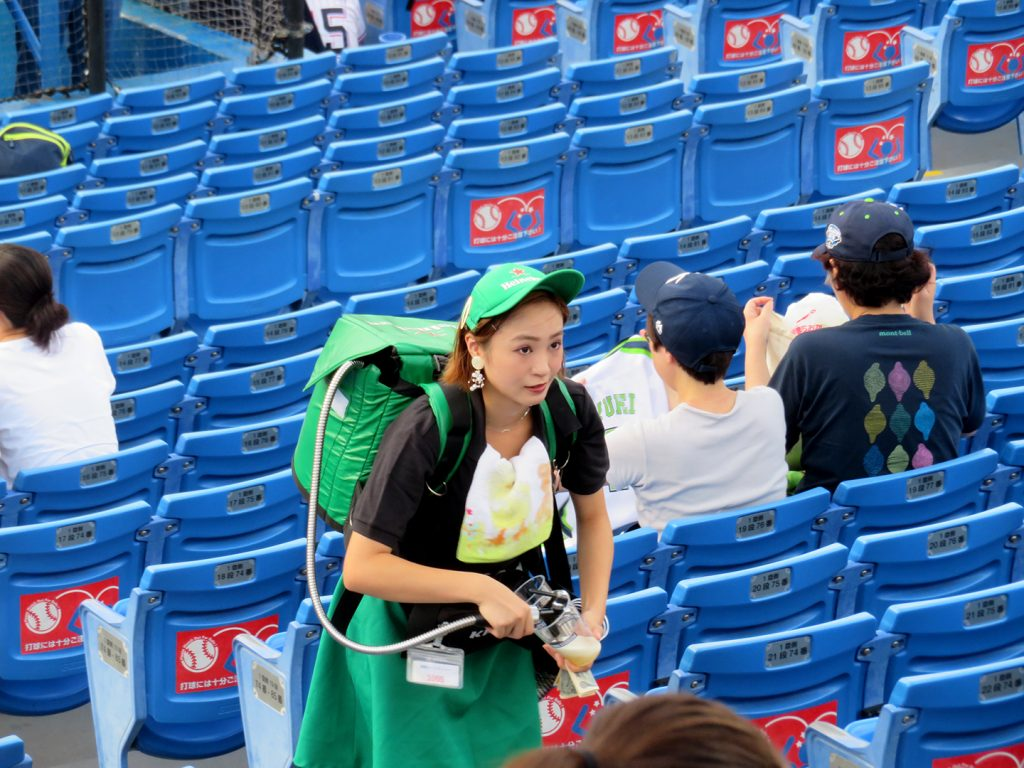 A young woman wearing a green hat with a small keg on her back pours a Heineken beer into a plastic cup.