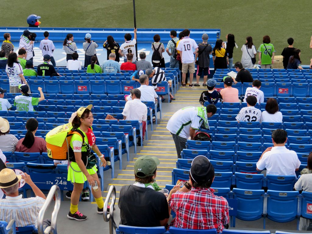A young woman wearing a neon green outfit with a Kirin hat and a small keg on her back walks through the stands at a Tokyo Yakult Swallows baseball game.