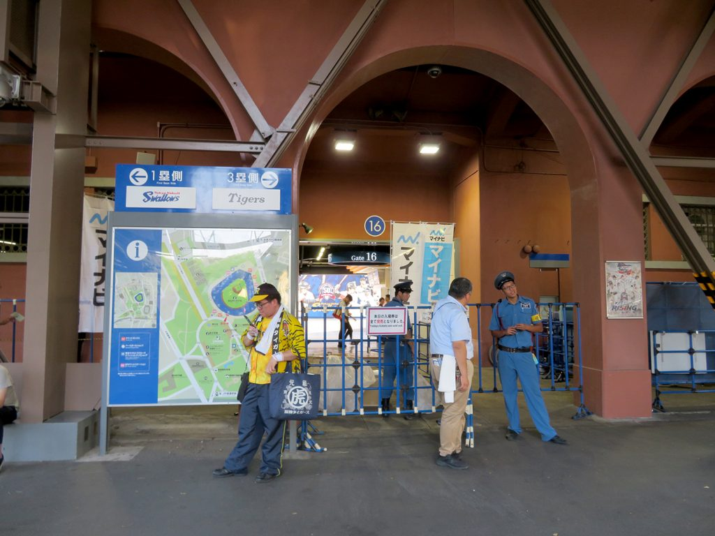 A few people stand in front of a map showing Meiji Jingu Stadium in front of the center field gate.