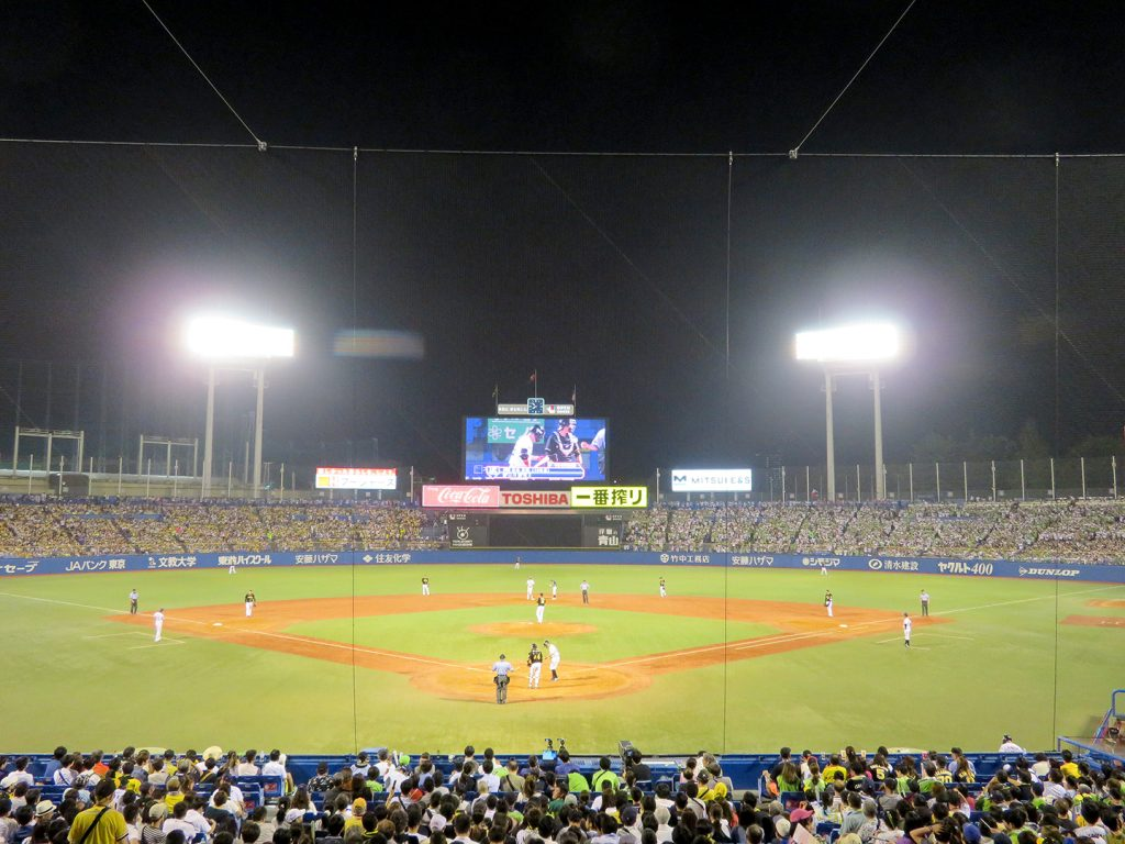 Overview of a baseball stadium from behind home plate with a large videoboard in center field.