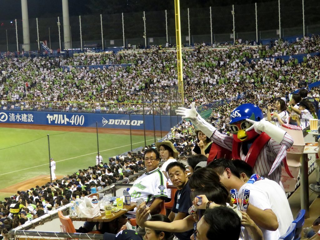 A person dressed as a swallow wearing a pinstripe baseball uniform poses with fans at a Tokyo Yakult Sallows baseball game.