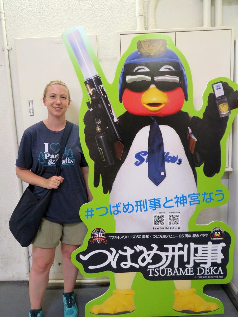 A woman stands next to a cutout of an anthropomorphic swallow holding a t-shirt cannon and a police badge.