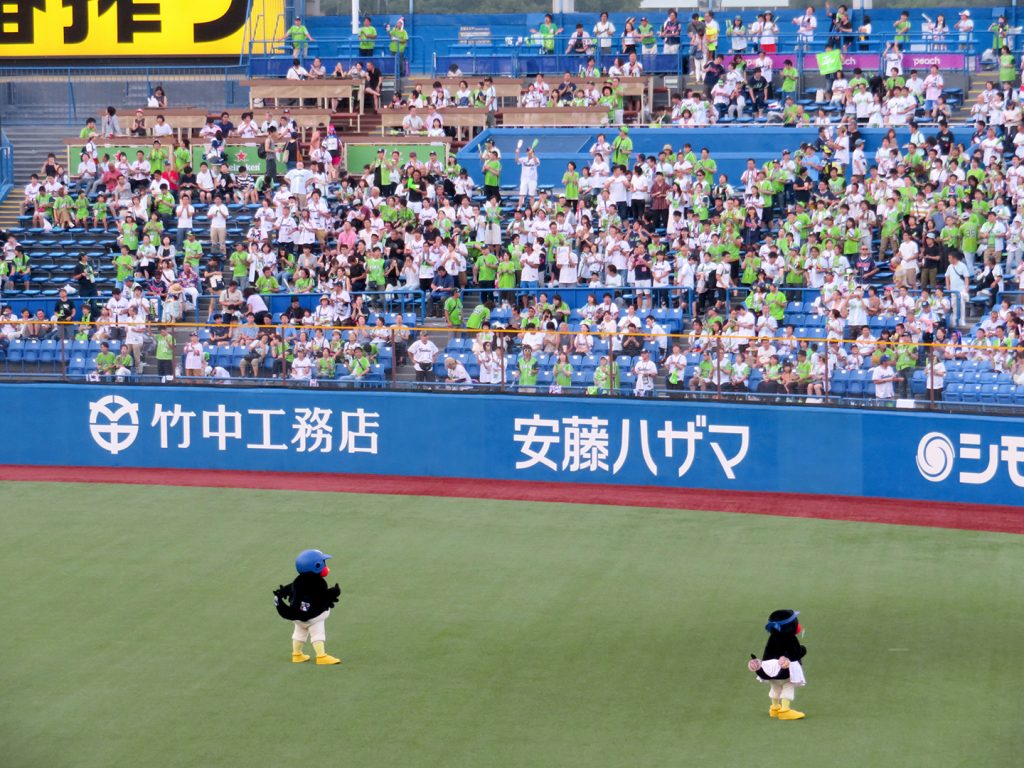 Two anthropomorphic swallows face the outfield stands while leading fans in cheers at a Tokyo Yakult Swallows baseball game.