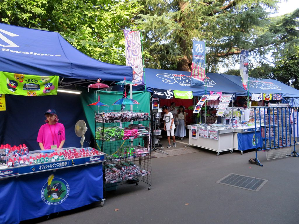 Two large tents over stands selling Tokyo Yakult Swallows items outside of the stadium.