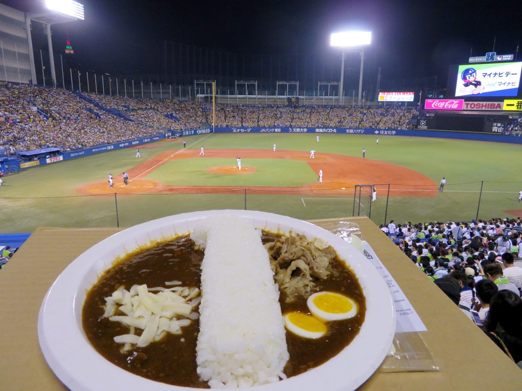 A plate with the number one formed in rice in the center with curry on either side, beef and a sliced boiled egg on the right, and a bit of shredded white cheese on the left.