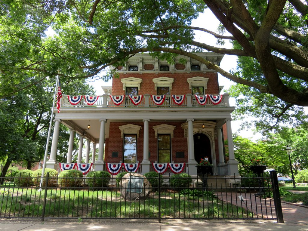 Exterior of a three-story Italianate brick house with red, white, and blue bunting on the first and second story patios.