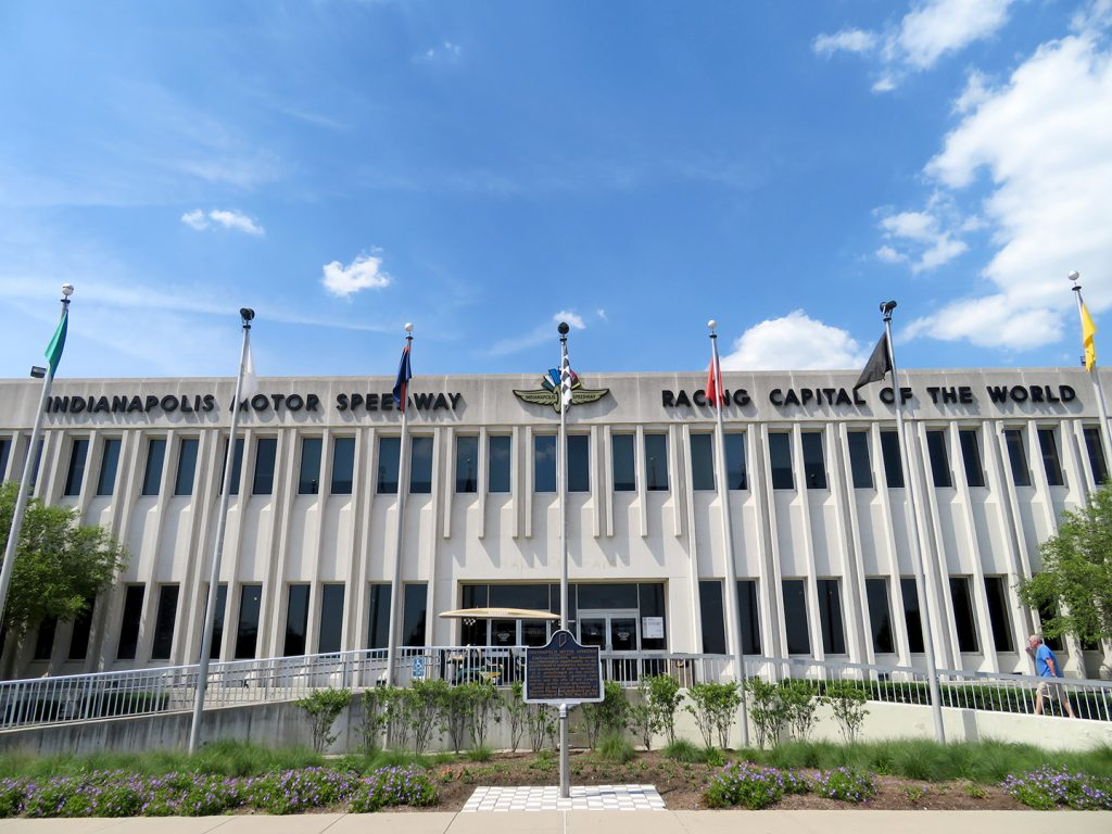 """Large concrete building with multiple flags in front of it. Text at top of building says """"Indianapolis Motor Speedway. Racing Capital of the World."""""""