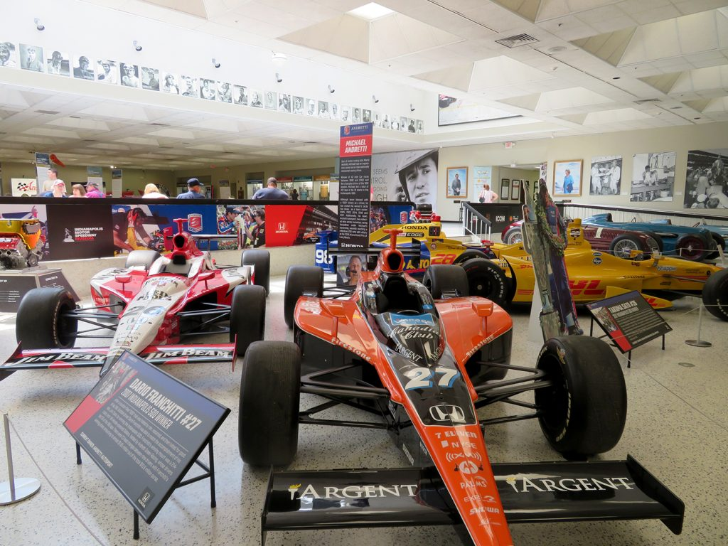 Four racecars around a sign denoting Michael Andretti's ownership of the Indianapolis 500 winning cars.