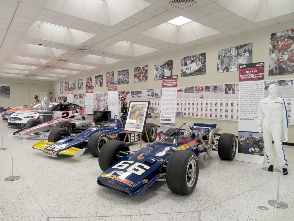 Three open-wheel racecars in front with three stock cars further back in front of a display showing winners of races at Indianapolis Motor Speedway.