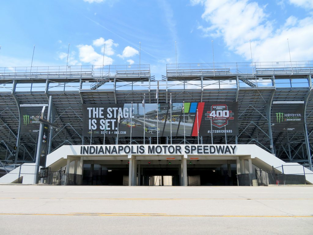"""Grandstand seating with banner beneath it that says """"Indianapolis Motor Speedway."""""""
