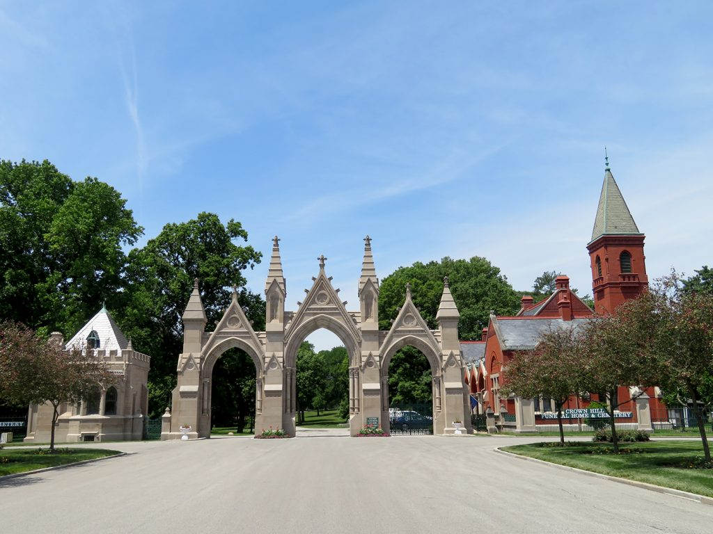 High Victorian Gothic limestone gate with a red-brick Gothic gatehouse on the right.