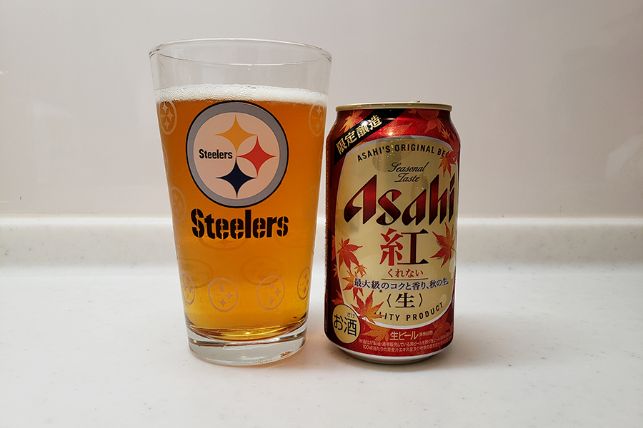 A pint glass full of a pale lager next to a can of Asahi Kurenai (紅) with fall leaves on the can.