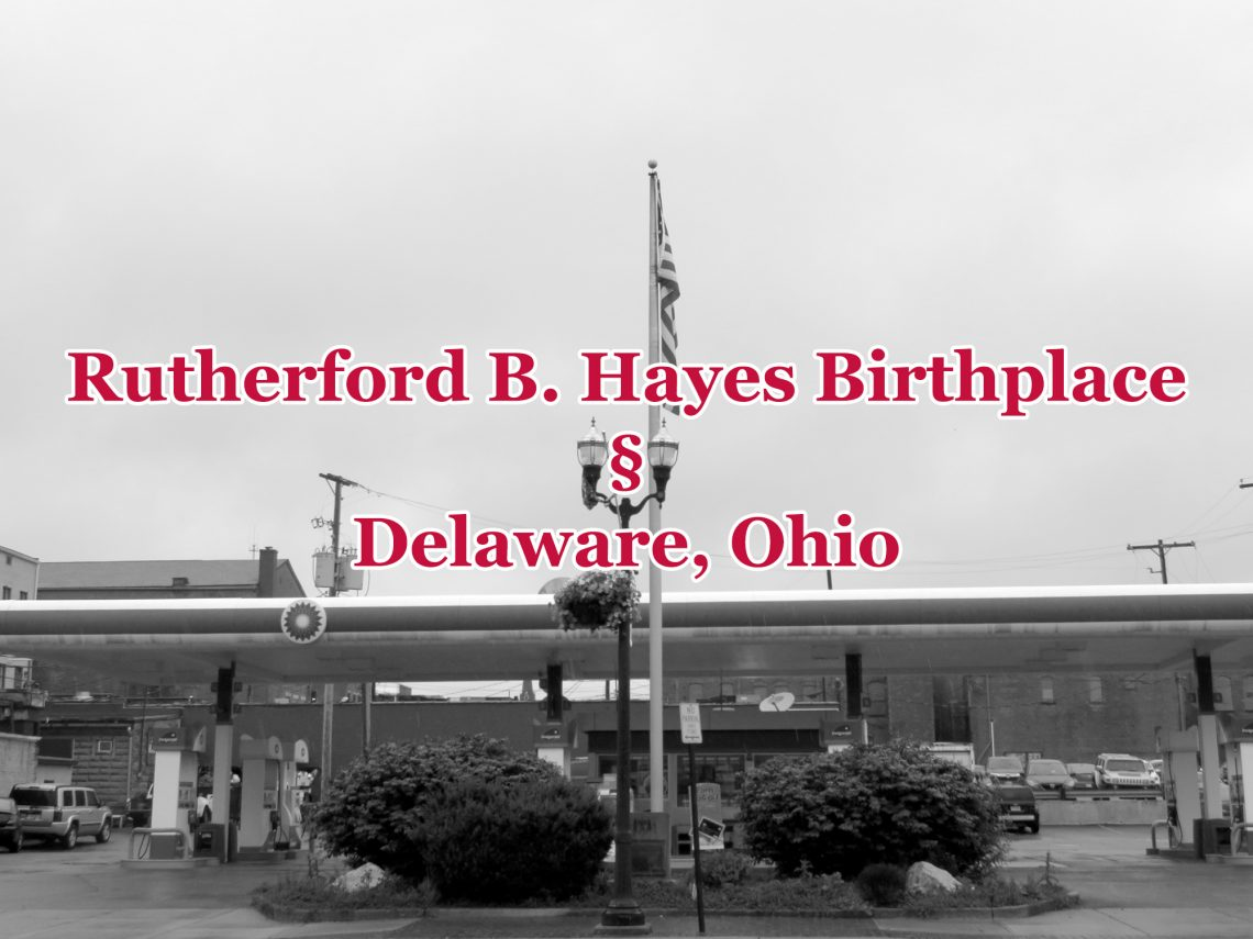 "Black-and-white photo with overview of a gas station with a large flag pole and red text overlaying the image that says ""Rutherford B. Hayes Birthplace. Delaware, Ohio."""