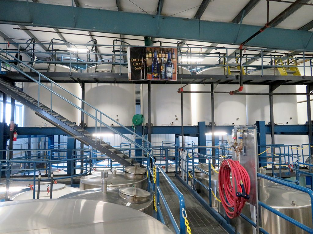 """Overview of multiple stainless steel and porcelain aging tanks with a banner that says """"Oregon craft sake."""""""
