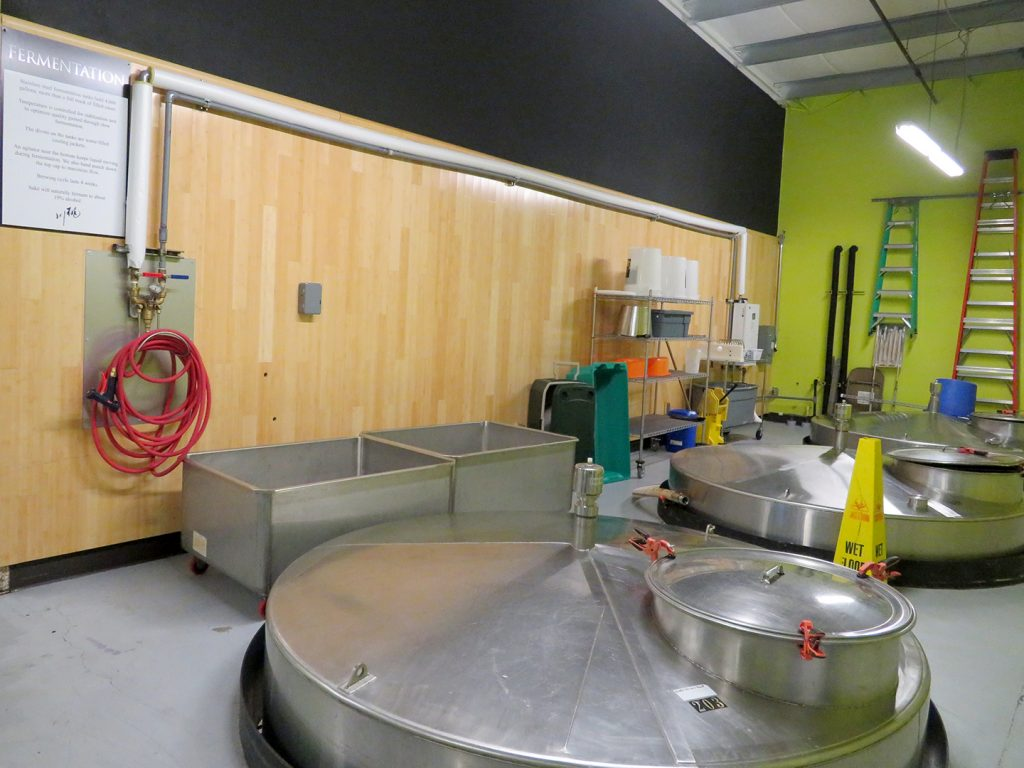 """Overview of several large stainless steel tanks with a sign to the left on a wall that says """"Fermentation,"""" which includes information about the fermentation of sake."""