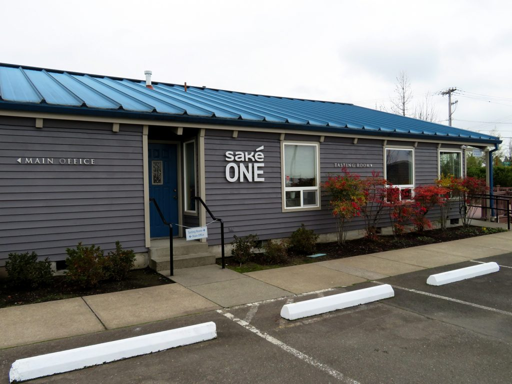 Exterior view of a building that say SakeOne with signs to the main office and the tasting room.