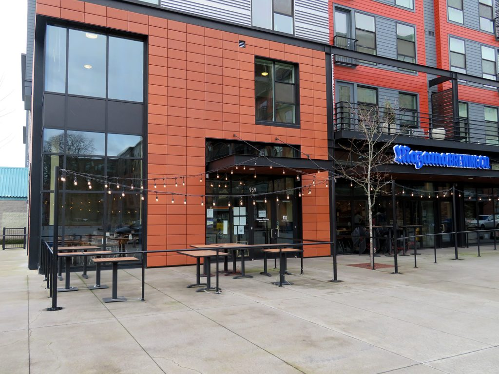 "Mixed-use building with a small patio and signage that says ""Mazama Brewing Co."" in blue letters."