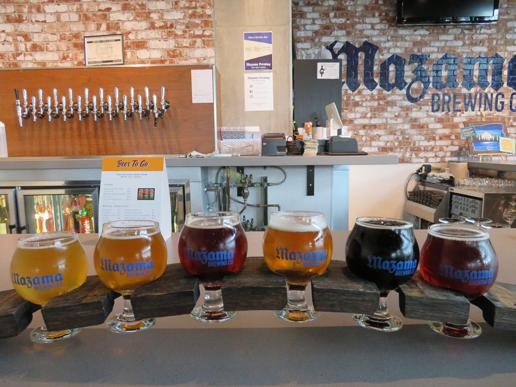 "A arched flight board with six tasting glasses on a bar top with ""Mazama Brewing Co."" on a brick wall in the background."
